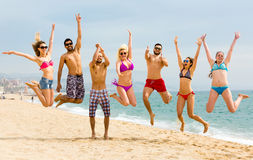 Happy people jumping on a beach Stock Image