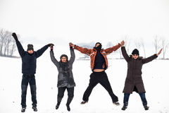 Happy people jumping in snow winter Royalty Free Stock Photo