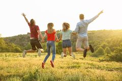 Happy people jumping in wilderness. Camping season Royalty Free Stock Images