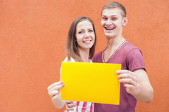 Happy people looking and holding frame at red background Royalty Free Stock Image