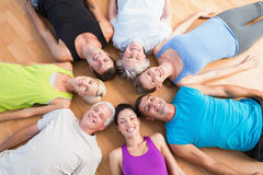 Happy people lying on hardwood floor at gym Royalty Free Stock Photo