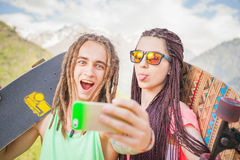 Happy people make selfie on mobile phone at mountain outdoor Stock Image