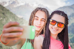 Happy people make selfie on mobile phone at mountain outdoor Stock Photography