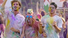Happy people moving to music at Holi festival, friends covered in colored paint. Stock footage stock video footage