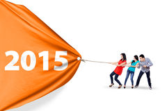Happy people pulling a banner 2015. Cheerful asian people collaborate to pull a banner of 2015, isolated over white background Stock Photo