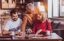 Happy people putting puzzles together royalty free stock photography