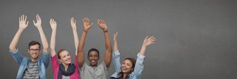 Happy people raising hands against wide blank grey. Digital composite of Happy people raising hands against wide blank grey Royalty Free Stock Photo