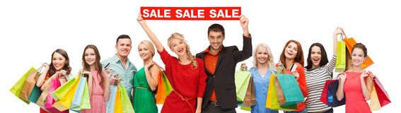 Happy people with red sale sign and shopping bags royalty free stock photography