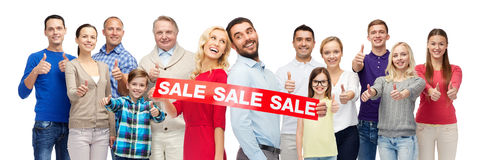 Happy people with red sale sign showing thumbs up. Gesture, sale, shopping and people concept - group of smiling men, women and kids showing thumbs up and Royalty Free Stock Photo