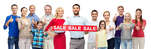Happy people with red sale sign showing thumbs up. Gesture, sale, shopping and people concept - group of smiling men, women and kids showing thumbs up and Royalty Free Stock Photography