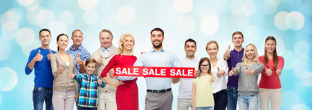 Happy people with red sale sign showing thumbs up Stock Photo