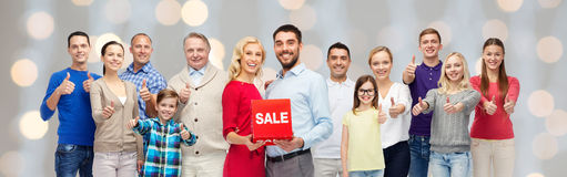 Happy people with red sale sign showing thumbs up. Gesture, sale, shopping and people concept - group of smiling men, women and kids showing thumbs up and Stock Images