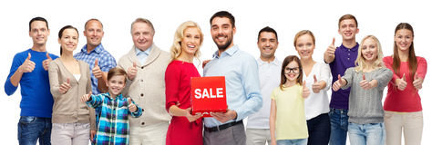 Happy people with red sale sign showing thumbs up. Gesture, sale, shopping and people concept - group of smiling men, women and kids showing thumbs up and Royalty Free Stock Image