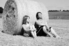 Happy people relaxing in nature on hay bales Stock Photos