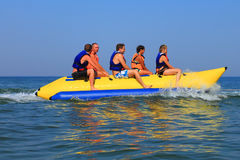 Happy people ride the inflatable watercraft banana Royalty Free Stock Photography