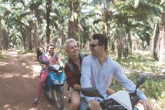 Happy People Ride Scooter Enjoy Summer Vacation While Road Trip Through Palm Trees Forest Two Couple Travel On Bikes. Together Adventure And Freedom Concept Stock Photos