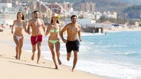 Happy people running at beach Stock Photo