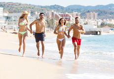 Happy people running at beach Stock Image