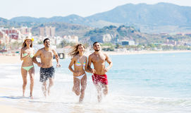 Happy people running at beach. Two couples running on the beach near the sea. Focus on the right couple stock photo