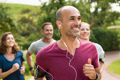 Happy people running. Portrait of a happy cheerful men listening to music while jogging. Man listening to music while jogging with group. Happy trainer in park Stock Photos