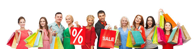Happy people with sale sign on shopping bags. Consumerism, people and discount concept - group of happy people with percentage and sale sign on shopping bags royalty free stock photos