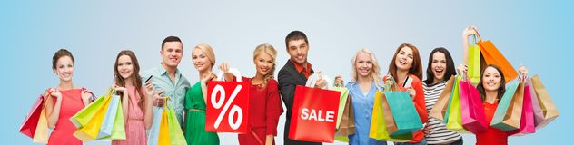 Happy people with sale sign on shopping bags. Consumerism, people and discount concept - group of happy people with percentage and sale sign on shopping bags stock photos