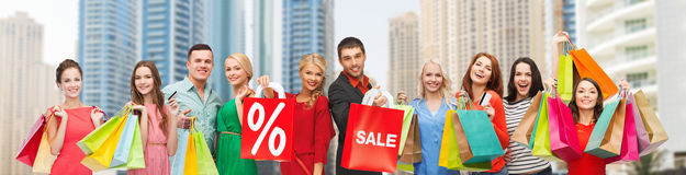 Happy people with sale sign showing thumbs up Royalty Free Stock Photo