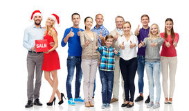 Happy people with sale sign showing thumbs up Royalty Free Stock Photography