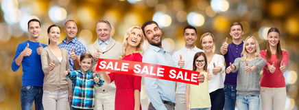 Happy people with sale sign showing thumbs up Royalty Free Stock Photos