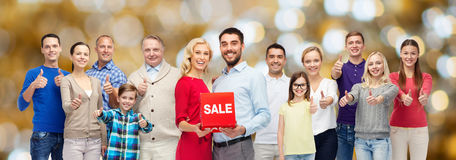 Happy people with sale sign showing thumbs up Stock Images