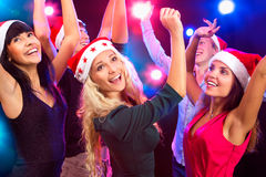 Happy people in Santa hats. Dancing at party Royalty Free Stock Photo