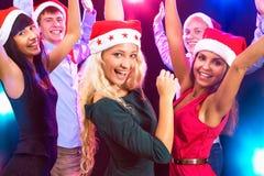 Happy people in Santa hats. Dancing at party Stock Photos