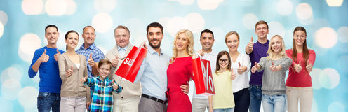 Happy people with shopping bags showing thumbs up Royalty Free Stock Photo