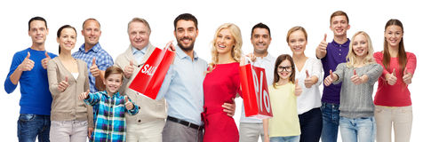 Happy people with shopping bags showing thumbs up Stock Images
