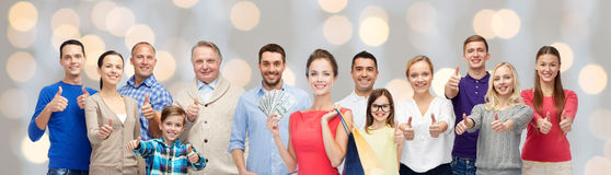 Happy people with shopping bags showing thumbs up Stock Image