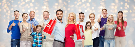 Happy people with shopping bags showing thumbs up Stock Photo