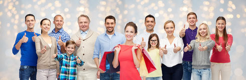 Happy people with shopping bags showing thumbs up. Sale, family, generation and people concept - group of happy men and women with shopping bags showing thumbs stock photography