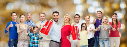 Happy people with shopping bags showing thumbs up royalty free stock photos