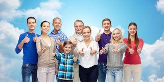 Happy people showing thumbs up over sky and clouds stock image