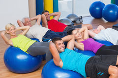 Happy people stretching on exercise balls. Portrait of happy people stretching on exercise balls in fitness club Stock Photos