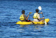 Happy people swimming in kayaks wearing lifejackets with paddle Royalty Free Stock Photography