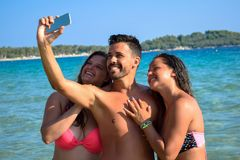 Happy people taking a selfie with cell phone at sea. stock image