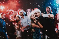 Happy People Taking Selfie on New Year Party. Happy New Year Concept. People Have Fun. Indoor Party. Celebrating of New Year. Young Woman in Dress. Young Man royalty free stock images