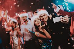 Happy People Taking Selfie on New Year Party. Happy New Year Concept. People Have Fun. Indoor Party. Celebrating of New Year. Young Woman in Dress. Young Man stock photo