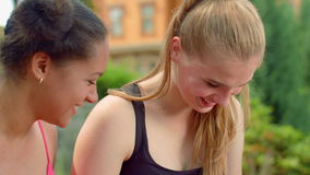Happy people talking outdoors. Multi ethnic women laughing. Two beautiful girls chatting in park. Closeup of blonde woman talking with mulatto girlfriend stock video