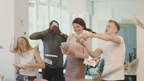 Happy people throwing dollars at coworking. Young people making rain with money. Happy people throwing away dollar banknote at coworking. Young people making stock footage