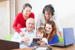 Happy  people  uses  various electronic devices in home Stock Photos