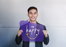Happy Person Concept. Young Man Smiling and Show I am Happy Text on Speech Bubble Card. Positive Human Face Expression. Good. Emotion stock photography