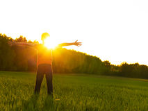 Happy person in the field with raised arms on the sunset Royalty Free Stock Photography