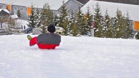 Happy person having fun joy sledging down the mountain ski slope Royalty Free Stock Images